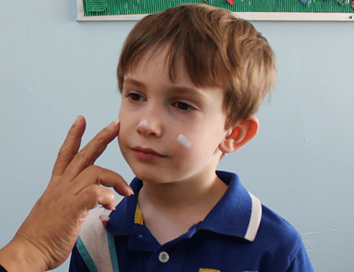 Teacher applies sunscreen to a child's face