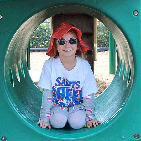 Sun safe girl in playground tunnel